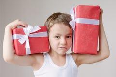 有两件礼物展示肌肉的男孩 图库摄影