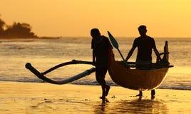 有两位渔夫的渔夫小船巴厘岛的,在日落期间的印度尼西亚在海滩 免版税库存照片
