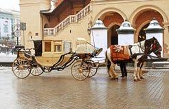 有两匹马的用马拉的支架在克拉科夫布料霍尔附近的老镇街道 免版税库存图片