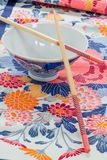 有两双筷子的中国饭碗在一块打印的布料 免版税库存照片
