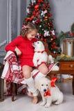 有两只小狗金毛猎犬的愉快的女孩在圣诞树背景  免版税图库摄影