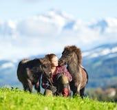 有两只微型舍特兰群岛小马的少妇 两匹马和美丽的夫人室外在山背景 免版税库存照片