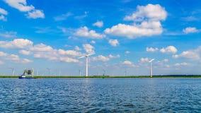 有两台和三台刃状的风轮机和一个渔船的风力场在湖 图库摄影