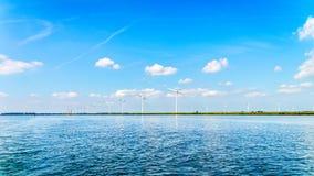 有两台和三台刃状的风轮机的风力场在沿Veluwemeer岸的一个大风力场  免版税库存照片