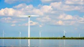 有两台和三台刃状的风轮机的风力场沿Veluwemeer岸  免版税库存图片