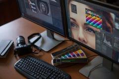 有两台显示器的桌面,键盘,照相机,日志,设计师的, retoucher,摄影师一个调色板 免版税库存照片
