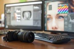 有两台显示器的桌面,键盘,照相机,日志,设计师的, retoucher,摄影师一个调色板 免版税图库摄影