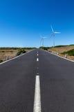 有两台风轮机的一条直路在与蓝天的区域 图库摄影