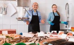 有两宜人的友好的selle的普通的鱼和海鲜商店 库存照片