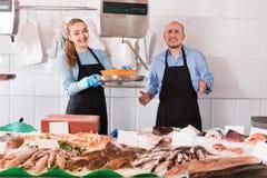 有两宜人的微笑的卖主的普通的鱼和海鲜商店 免版税库存图片