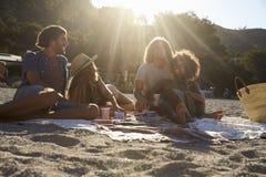 有两对的夫妇在海滩,由后照的,接近的一顿野餐 免版税图库摄影