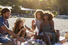 有两对的夫妇在海滩,透镜火光,伊维萨岛的一顿野餐 免版税库存图片