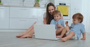 有两小孩子的一个进步年轻母亲与她的父亲谈话通过视频通信 现代技术 股票视频