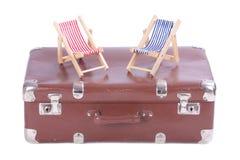 有两张玩具海滩睡椅的葡萄酒皮革手提箱 库存照片