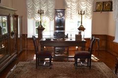 有两把扶手椅子的老室在桌和书橱附近 内部空间 库存照片