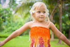 有两朵热带花的可爱的女孩在耳朵后在公园 免版税库存图片