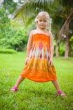 有两朵热带花的可爱的女孩在耳朵后在公园 免版税库存照片
