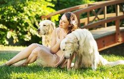 有两条狗的可爱的妇女 免版税库存图片