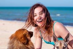 有两条狗的愉快的女孩在海滩 一个美丽的女孩笑并且拥抱狗 一只流浪狗和一名愉快的妇女 库存照片