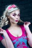 有两条猪尾的美丽的白肤金发的女孩,有创造性的玩偶构成的:桃红色光滑的嘴唇,佩带的桃红色最基本的礼服 对尊敬 库存照片
