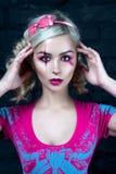 有两条猪尾的美丽的白肤金发的女孩,有创造性的玩偶构成的:桃红色光滑的嘴唇,佩带的桃红色最基本的礼服 对尊敬 图库摄影