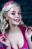 有两条猪尾的美丽的白肤金发的女孩,有创造性的玩偶构成的:桃红色光滑的嘴唇,佩带的桃红色最基本的礼服 对尊敬 免版税库存照片