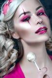 有两条猪尾的美丽的白肤金发的女孩,有创造性的玩偶构成的:桃红色光滑的嘴唇,舔lollipo的佩带的桃红色最基本的礼服 免版税库存照片