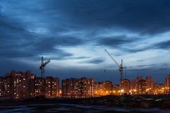 有两架塔吊的建筑工地以多层的房子和蓝天,夜场面为背景 库存图片