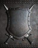 有两的中世纪盾横渡了在装甲背景的剑 库存照片