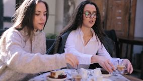 有两美丽的年轻女人坐在桌上在咖啡馆或餐馆和倒牛奶的早餐妇女对 影视素材