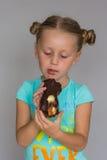 有两褶的女孩咬住巧克力蛋糕的 免版税图库摄影