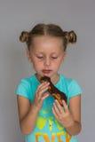 有两褶的女孩咬住巧克力蛋糕的 免版税库存图片
