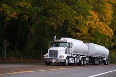 有两辆坦克拖车的白色大半船具卡车在秋天路 免版税库存照片