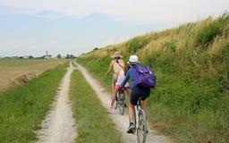 有两辆自行车的三个人沿在natur的周期道路 免版税库存图片