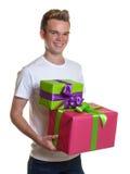有两件五颜六色的圣诞节礼物的英俊的人 免版税图库摄影