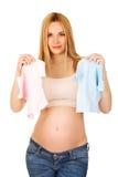 有两件小婴孩衬衣的孕妇 图库摄影