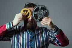 有两16mm影片轴的有胡子的人 免版税库存照片