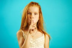 有严密的神色的红发女孩投入她的手指到嘴唇,展示秘密,并且机密,不告诉任何人 图库摄影