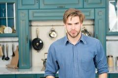 有严肃的面孔的人在蓝色衬衣立场在厨房里 免版税库存照片