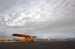 有严重的天空的黄色Cub飞机 库存图片