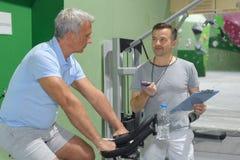 有个人教练员的资深火车在健身房 免版税图库摄影