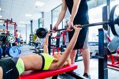 有个人教练员的妇女在长凳压入健身房 库存照片