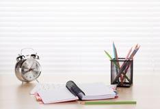 有个人计算机、笔记薄、警报和铅笔的办公室工作场所 库存图片