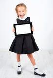 有个人计算机片剂的逗人喜爱的女小学生 库存照片