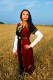 有中世纪礼服身分的微笑的少妇 免版税库存图片