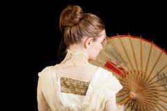 从有中国伞的后面看见的维多利亚女王时代的礼服的女孩 库存照片