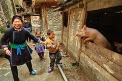 有中国农夫,在猪圈附近的立场的孩子的家庭。 免版税库存图片