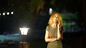 有中年的白肤金发的卷发的一名苗条哀伤的妇女谈话在电话在一个明亮的灯笼晚夏晚上附近 股票视频