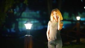 有中年立场的轻的卷发的一名苗条甜妇女在街道上的夏天晚上末期在明亮附近 股票录像