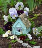 有中提琴和雏菊的小神仙的房子在庭院里开花 免版税库存图片